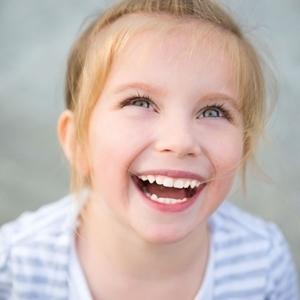 девочка сильно смеется аш видно зубы и смотрит вверх