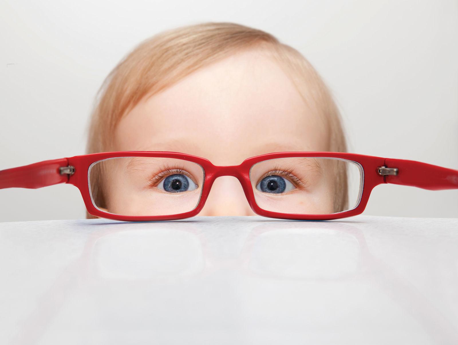 на столе лежат красные очки и сквозь них смотрит маленький мальчик
