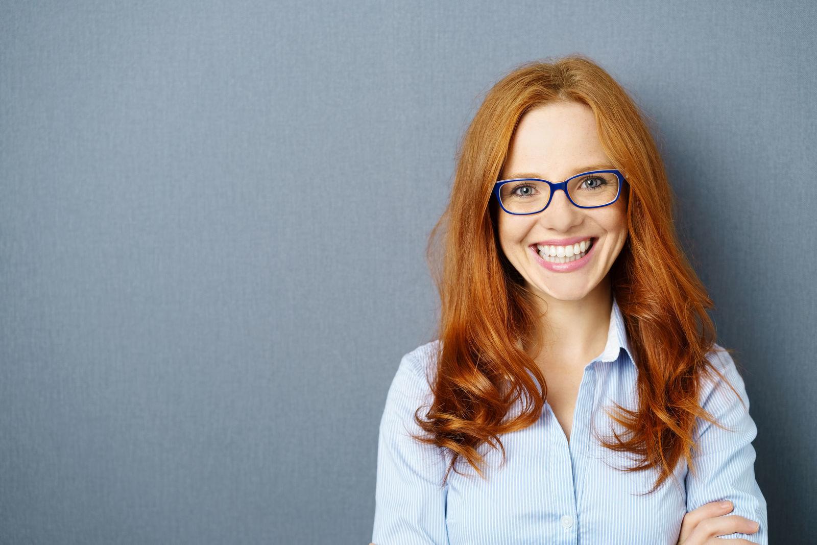 рыжая девушка улыбается в очках у нее хорошее зрение