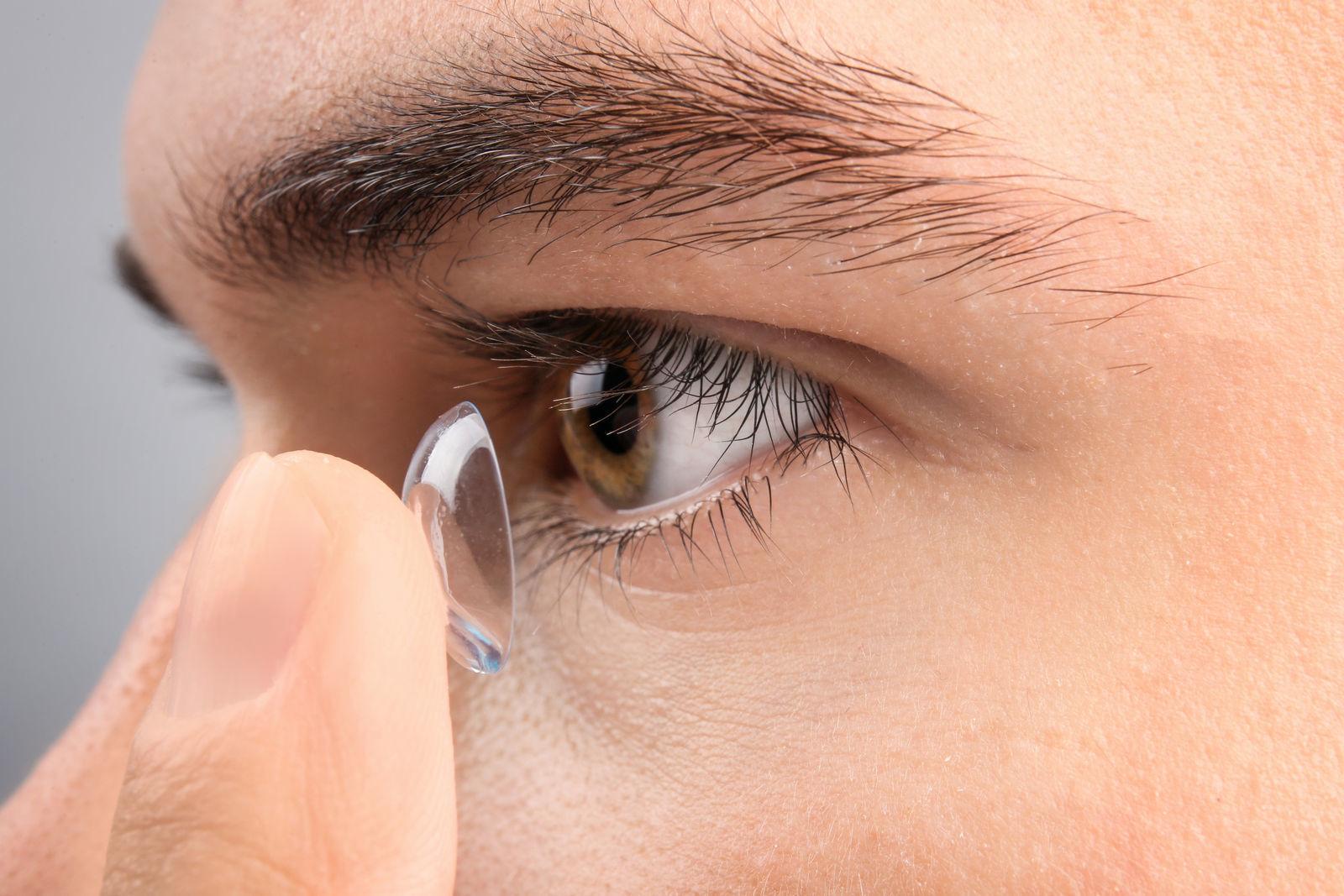 подросток надевает контактную линзу себе на глаз крупный план сбоку