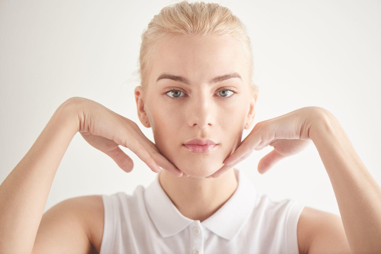 девушка блондинка поддерживает лицо руками белая комната пристальный здоровый взгляд