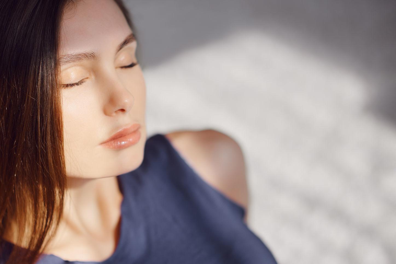 девушка в солнечных лучах закрыла глаза и дает зрению отдохнуть