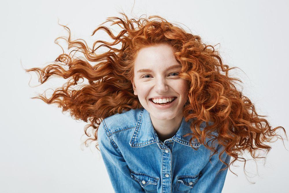 девушка смеется у нее рыжие волосы белый фон кудри