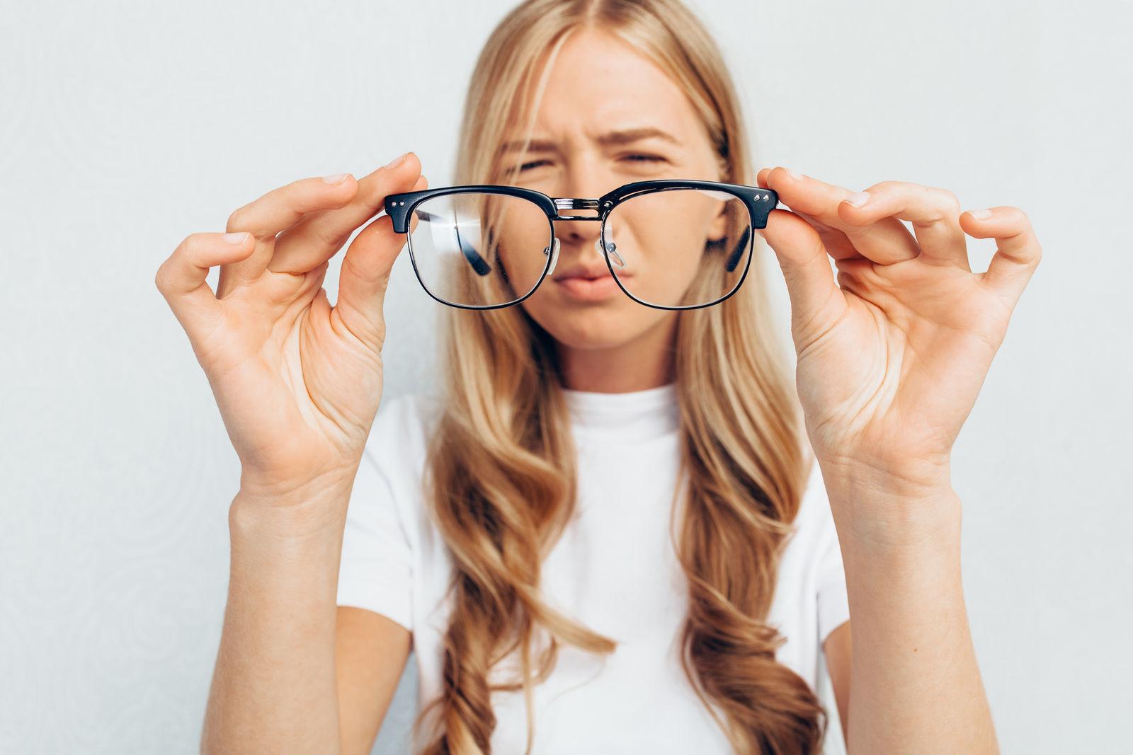 девушка держит в руках очки и щурится