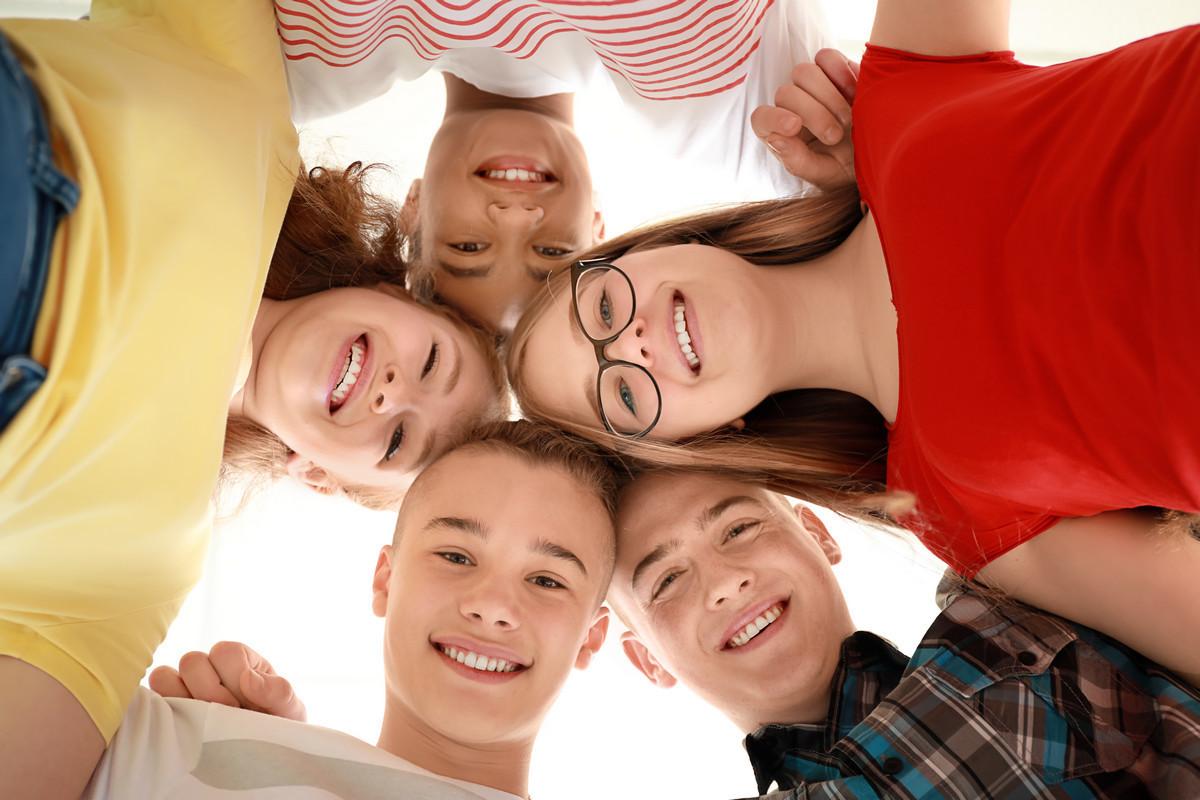 группа школьников собрались в круг и смотрят сверху вниз обнявшись друг с другом хоровод школьников