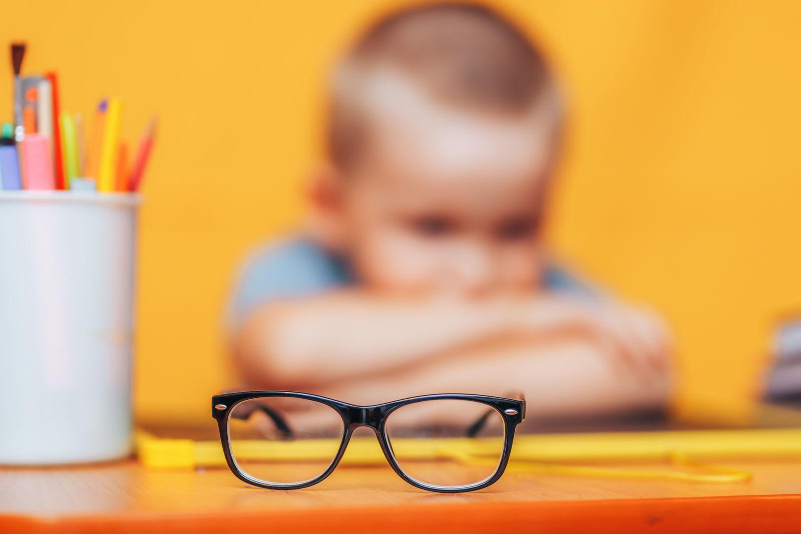 мальчик сидит за столом на фоне оранжевой стены на первом плане очки
