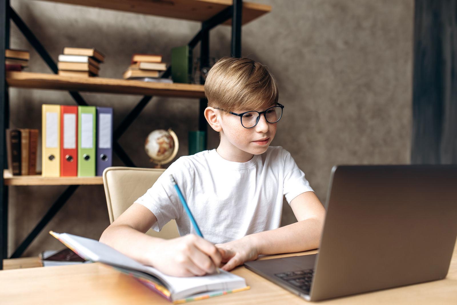 мальчик в очках сидит за учебным столом и делает домашнее задание учится