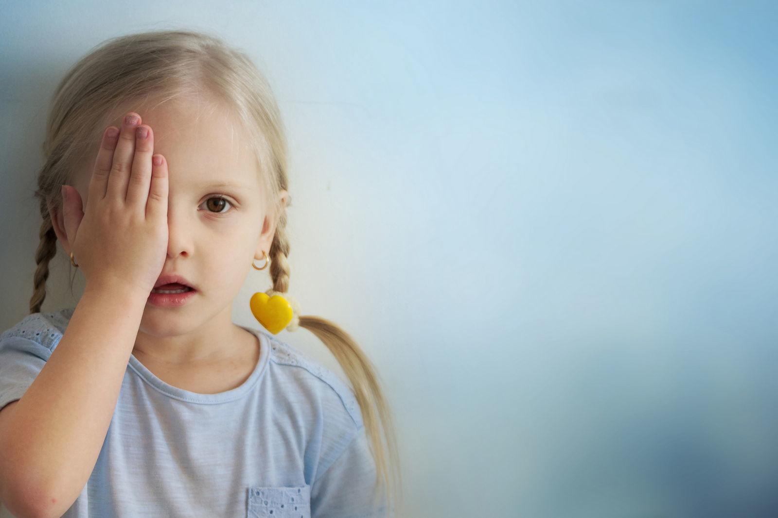 девочка стоит возле стены и прикрывает рукой один глаз