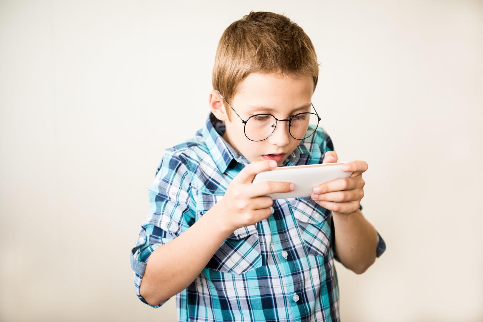 мальчик в очках играет в игры на приставке