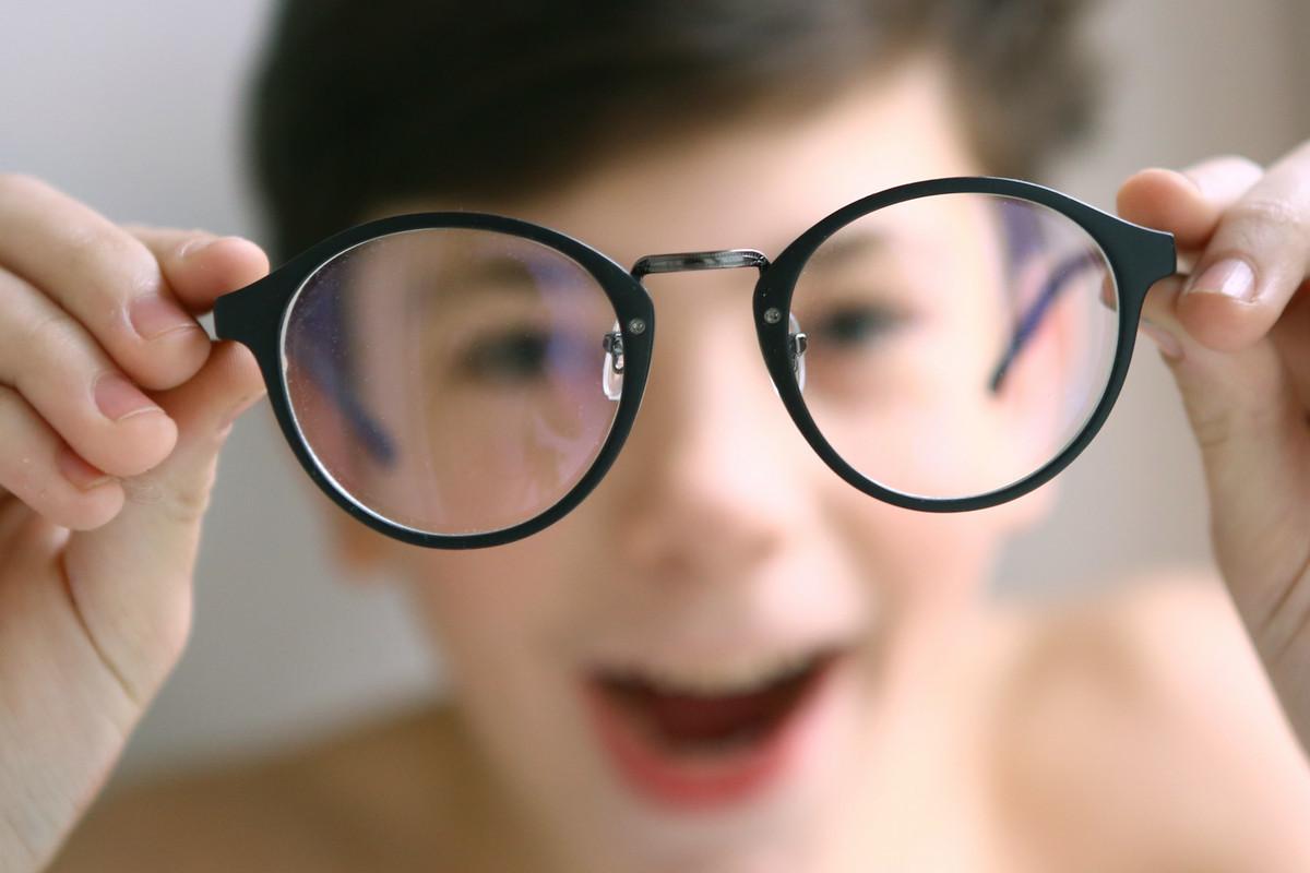 крупным планом очки показывает мальчик держим в руках лицо у него размытое на заднем плане