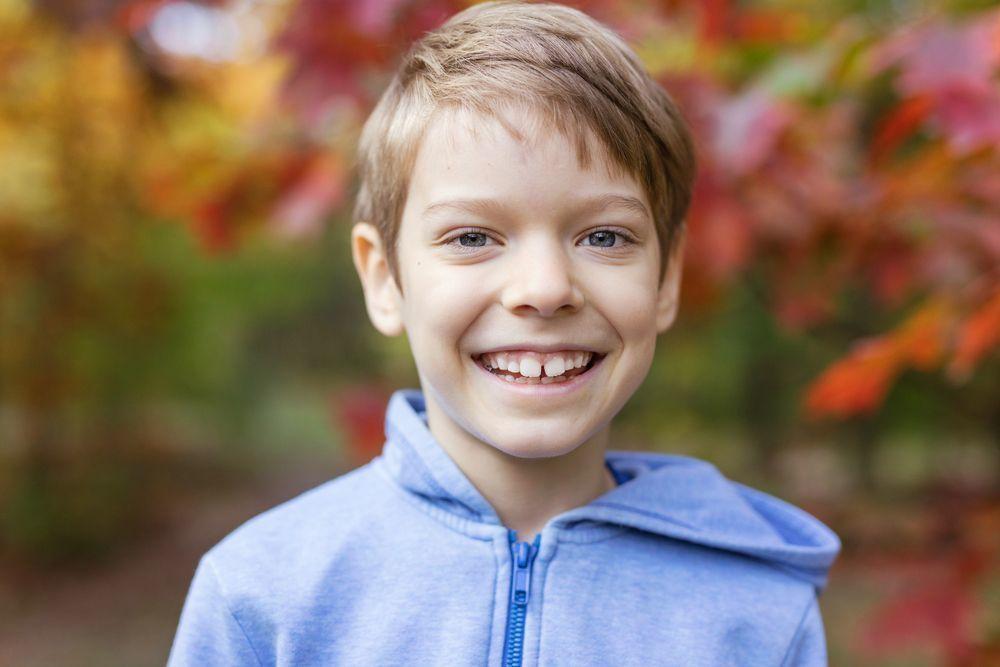 мальчик улыбается на фоне осенних листьев
